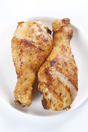 crispy: Two roasted chicken legs on plate on white background Stock Photo