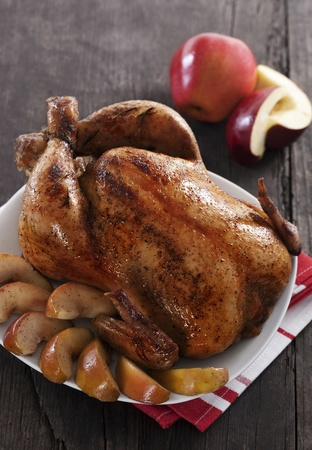 veggie tray: Roasted chicken with apples on wooden table Stock Photo