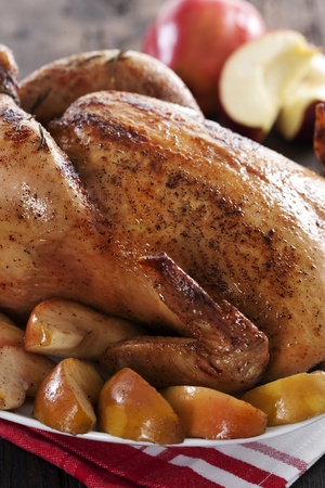 Roasted chicken with apples on wooden table photo