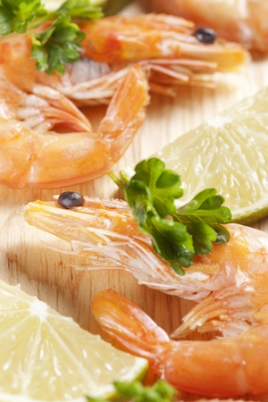 Shrimps on board with parsley and lemon wedges photo