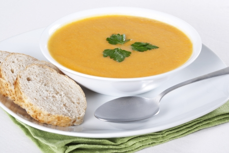 soup bowl: A bowl of soup and few slices of bread Stock Photo