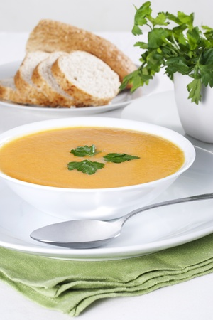 A bowl of soup with parsley and few slices of bread