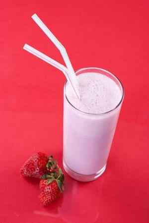 Strawberry milkshake with fresh fruit on red background  photo