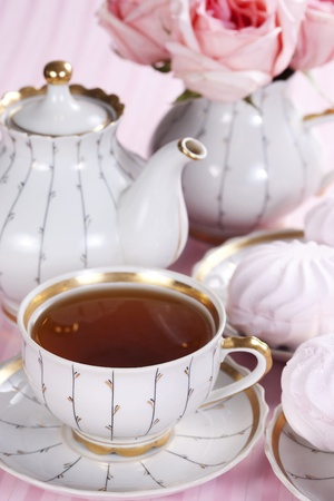A cup of tea, teapot, sweets and a bouquet of roses on a pink background photo