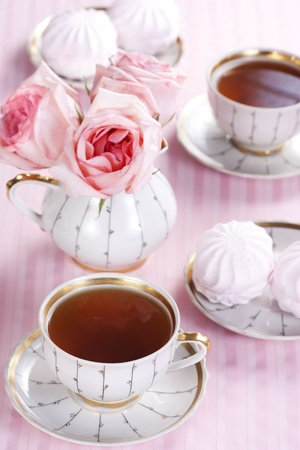 Two cups of tea, sweets and a bouquet of roses on a pink background Stock Photo - 9254905