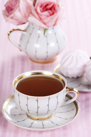 A cup of tea, sweets and a bouquet of roses on a pink background photo