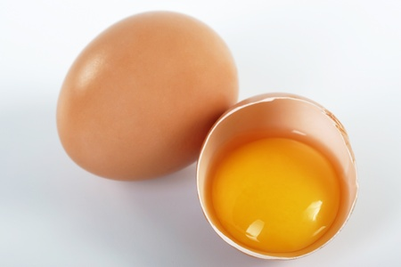 yolks: Two brown eggs on a white background. One egg is broken.