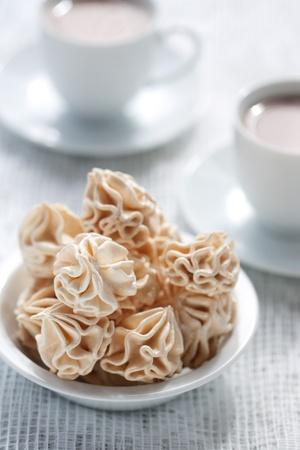 Meringues and two cups of chocolate drink photo