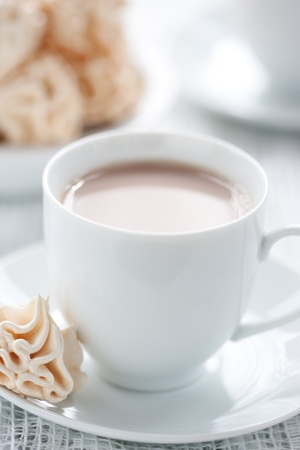Meringues and cup of chocolate drink, shallow dof. photo