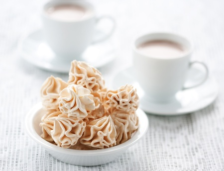 Meringues and two cups of chocolate drink, shallow dof. photo