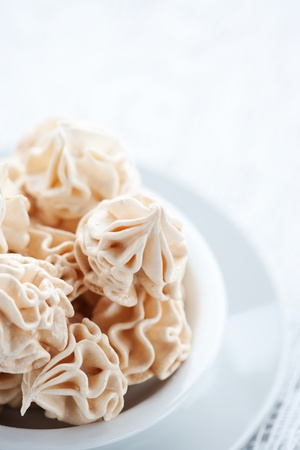 Meringues on white tablecloth photo