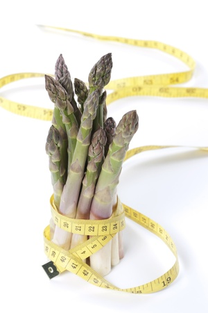 Raw asparagus and measuring type isolated on a white background photo
