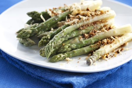 Asparagus gratin on white plate on blue background Stock Photo