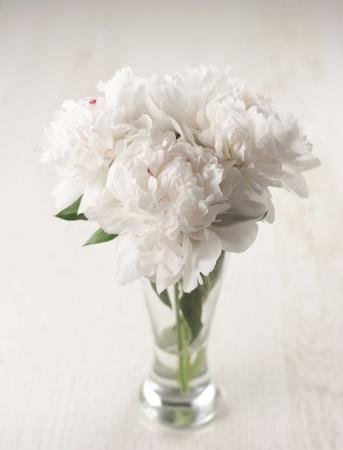 Vase of beautiful peony flowers on wooden background photo