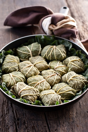 Rustic food, armenian or greek dolmades wrapped with rhubarb leaves, meat and rice