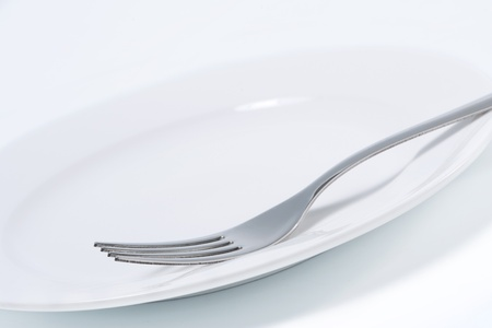 completed: Empty white plate and fork Stock Photo