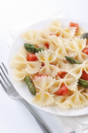 Pasta farfalle, tomato and asparagus salad on white background  photo