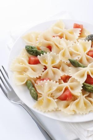 Pasta farfalle, tomato and asparagus salad on white background  photo