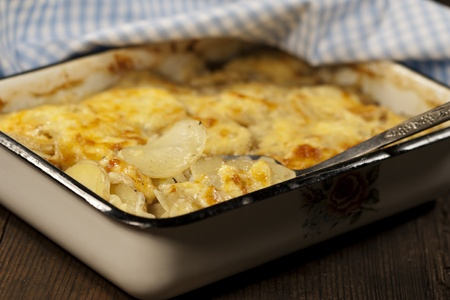 Potato gratin dauphinoise in the pan on rustic background photo