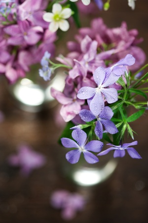 Beautiful spring flowers in a vase on wooden background photo