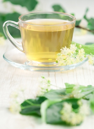 Cup of tea and linden flowers on wooden background photo