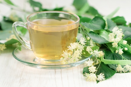 medicinal: Cup of tea and linden flowers on wooden background