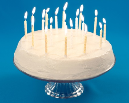 Birthday cake with burning candles on blue background