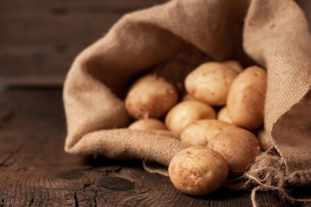 papas: Las patatas de la cosecha en saco de arpillera en el fondo r�stico Foto de archivo