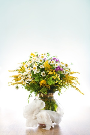Beautiful bouquet of wildflowers in vase on blue background Stock Photo - 14842382