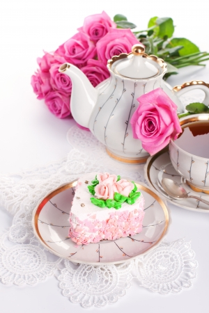 Closeup of heart-shaped cake with roses and cup of tea photo