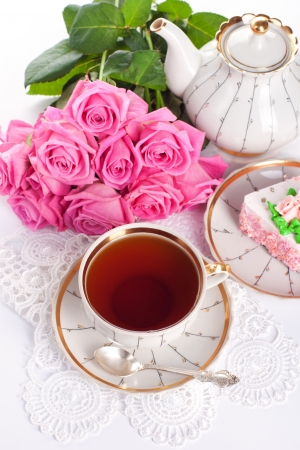 afternoon: Closeup of cup of tea with cake and roses