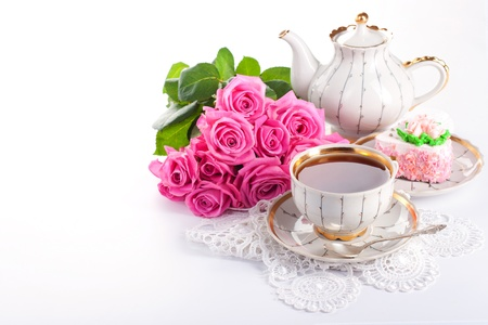 teacup: Closeup of cup of tea with cake and roses