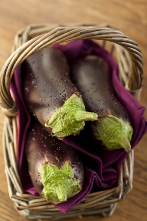 Raw aubergines or eggplants in basket on wooden backround. photo