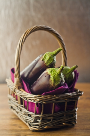 Raw aubergines or eggplants in basket on wooden backround. Stock Photo - 14953909