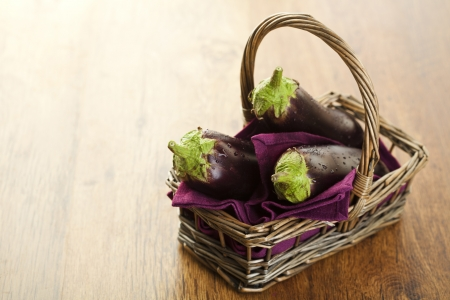 Raw aubergines or eggplants in basket on wooden backround. Stock Photo - 14953903