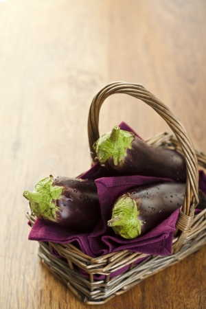Raw aubergines or eggplants in basket on wooden backround. Stock Photo - 14953905
