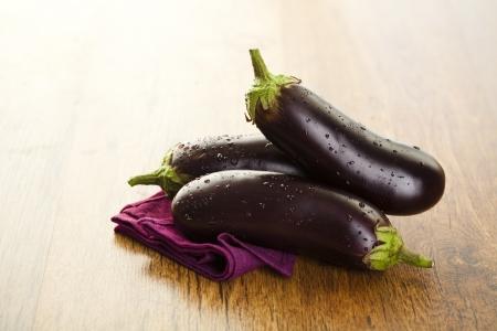 Raw aubergines or eggplants on wooden backround. Stock Photo