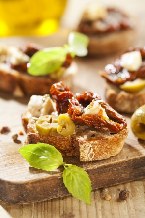 Italian appetizer bruschetta with olive oil, olives, sun-dried tomatoes and cheese. Stock Photo - 18151084