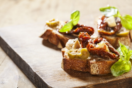 Italian appetizer bruschetta with olive oil, olives, sun-dried tomatoes and cheese. Stock Photo - 18151065