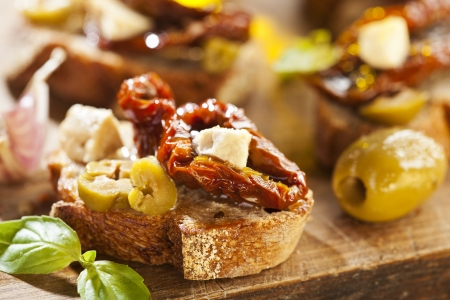 Italian appetizer bruschetta with olive oil, olives, sun-dried tomatoes and cheese Stock Photo - 18151085
