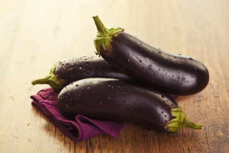 Raw aubergines or eggplants on wooden backround  Stock Photo - 18151066