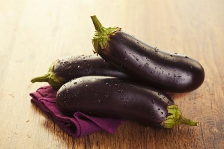 Raw aubergines or eggplants on wooden backround Stock Photo - 18151066
