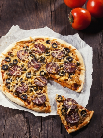 Sliced tasty salami pizza on rustic background Stock Photo - 18151053