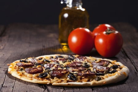 Sliced tasty salami pizza on rustic background Stock Photo - 18151043