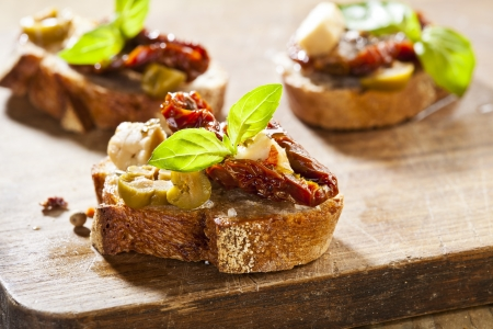 Italian cuisine appetizer bruschetta with tomatoes, olives and cheese Stock Photo - 18372118