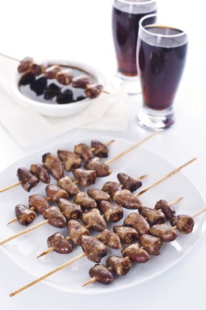 Grilled chicken hearts on skewers with soy sauce and salad. photo