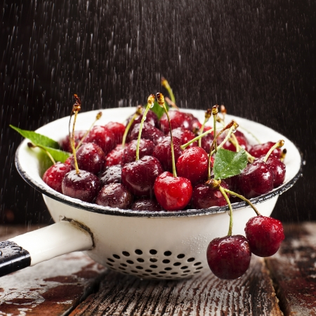 a colander: Fresh red cherries being washed in colander  Stock Photo