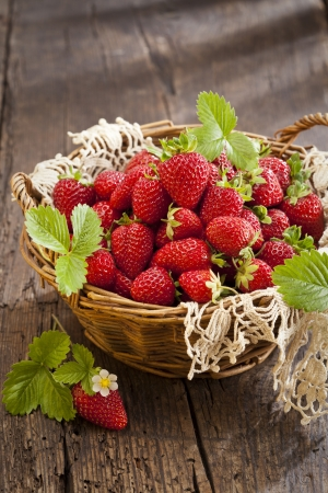 Strawberries in basket on rustic wooden background photo