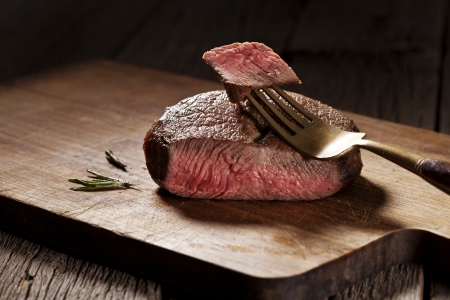 rib eye: Beef steak cooked to medium rare on wooden background Stock Photo