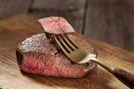 ribeye: Beef steak cooked to medium rare on wooden background Stock Photo